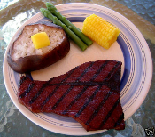 grilled steak, open baked potato with butter, corn on the cob, asparagus
