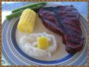 Fake Wax Steak Dinner with mashed potato, butter, corn on the cob and 2 asparagus spears